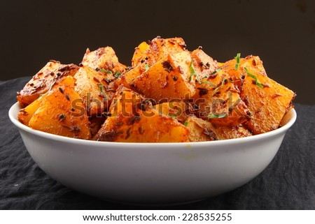Fried potatoes with herbs and spices.shallow depth of field photograph.  - stock photo