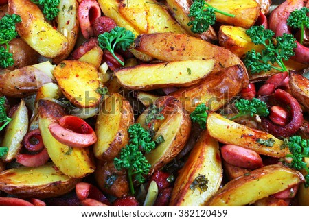 Fried potatoes with onion, sausages and green parsley. - stock photo