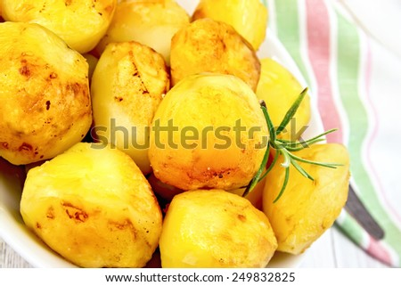 Fried potatoes with rosemary in a white plate, napkin, fork on the background light wooden boards - stock photo