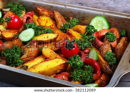 Fried potatoes with sausages, green parsley, fresh tomatos and cucumbers. Greasy pan on old wooden table. - stock photo