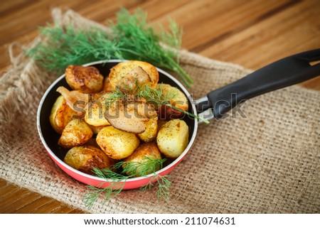 fried potatoes with slices of bacon in a frying pan - stock photo