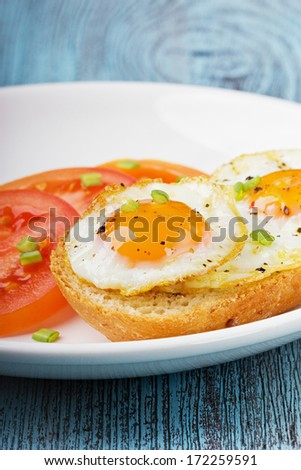 Fried quail eggs with a toast and tomatoes strewed with fresh green onions in a white plate on a wooden turquoise surface