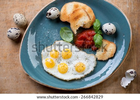 Fried quail eggs with toasts for breakfast, above view - stock photo
