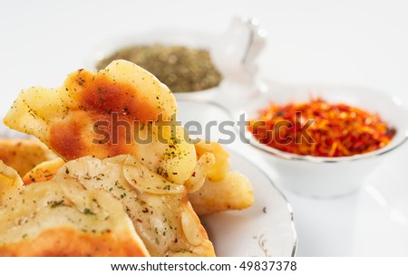 Fried ravioli in plate, aromatic herb and saffron in background - stock photo