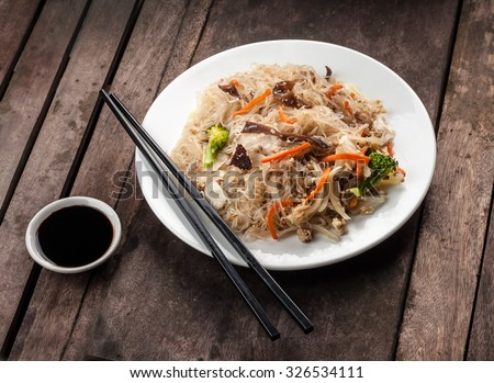 Fried rice noodles with chicken, vegetables and black mushrooms - stock photo