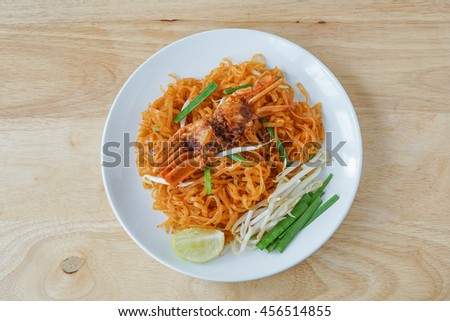 Fried rice noodles with chili sauce and crab on white plate, pad thai sen jan - stock photo