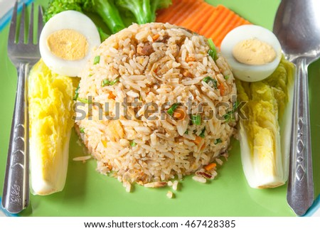 Fried rice with boiled egg and vegetable.