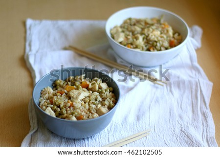 Fried rice with chicken and various vegetables, in two bowls with chopsticks. Selective focus.