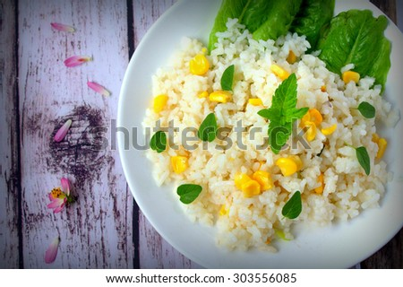 Fried rice with corn on wooden background