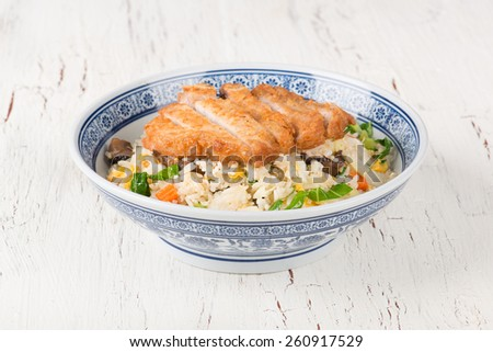 Fried rice with fried pork in china bowl on background - stock photo