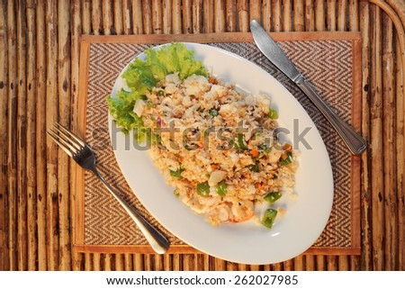 Fried rice with seafood on white plate on bamboo table top view 2 - stock photo