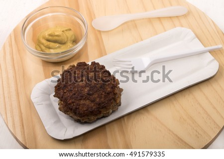 fried rissole on a paper plate, mustard in a glass bowl, plastic fork and spoon on wooden board