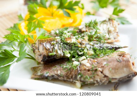 fried river fish with garlic and herbs, close up - stock photo