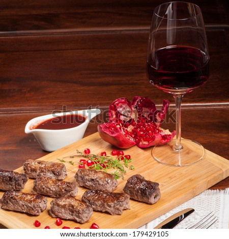 Fried rolls of pork with sweet garnet sauce - stock photo