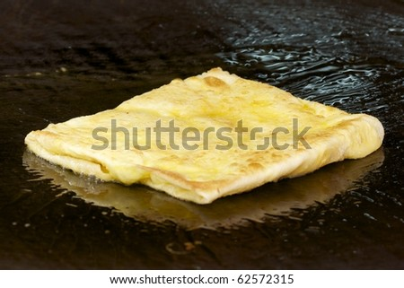 fried roti on oily hot steel plate - stock photo