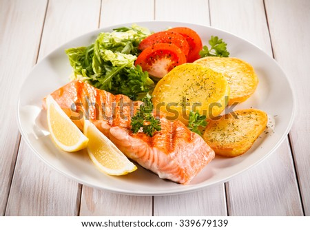 Fried salmon and vegetables on white background  - stock photo