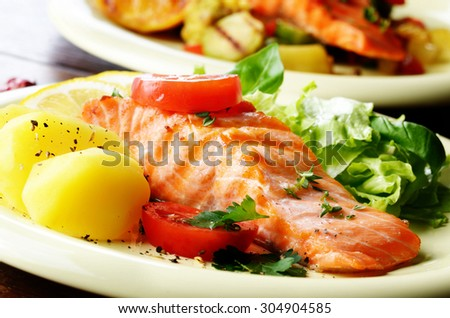 Fried Salmon fillet with boiled potato and lettuce on plate closeup