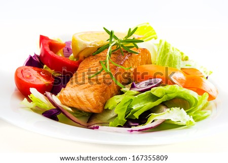 fried salmon fish with fresh salad on white plate - stock photo