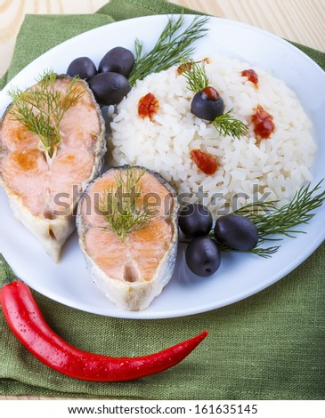 Fried salmon with rice, black olives and red chilli
