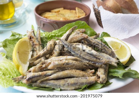 Fried sardines wth lemon pieces on a plate - stock photo