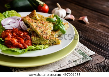 Fried savory zucchini pancakes, served with tomato salsa