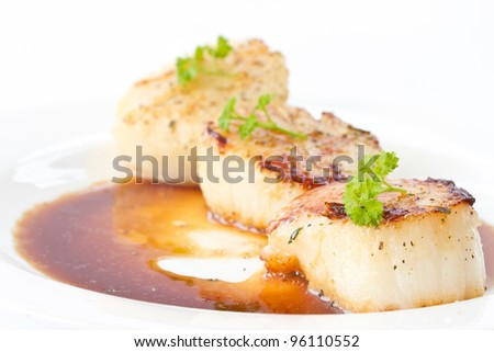 fried scallops with soy sauce on white plate - stock photo