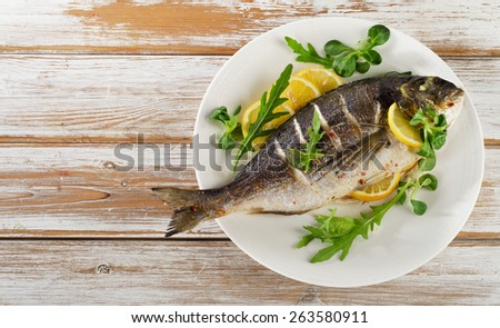 Fried sea bream on plate with  a lemon.  Healthy food. - stock photo