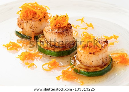Fried sea scallops with orange zest in plate - stock photo
