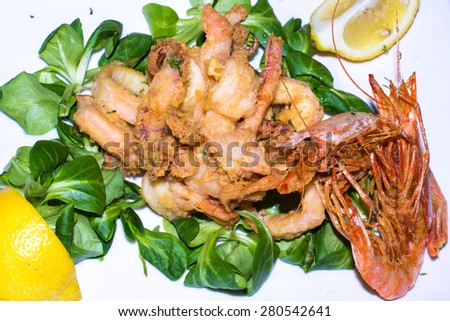 Fried seafood of shrimp and squid with salad and  lemon, typical italian food - stock photo