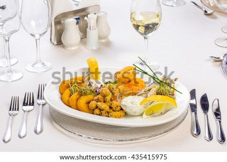 fried seafood plate with sauces  on a classy restaurant table
