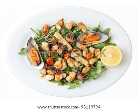 fried seafood with vegetables on white dish isolated over white background. Top view