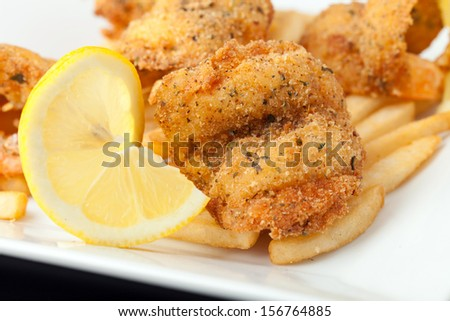 Fried shrimp and french fries plate garnished with lemon. - stock photo