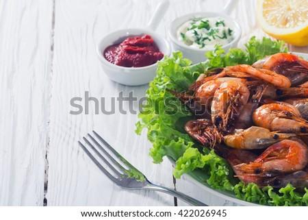 Fried shrimp with lemon & salad on wooden background - stock photo
