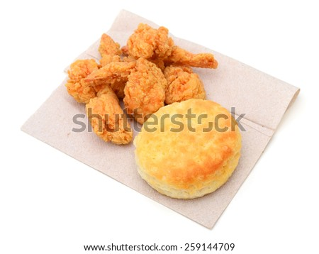 fried shrimps and one biscuit on paper isolated on white