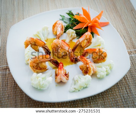 Fried shrimps on a plate with vegetables and sauces. Restaurant