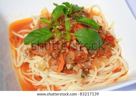 Fried spaghetti with tomato sauce and chopped meat. The meal is ...