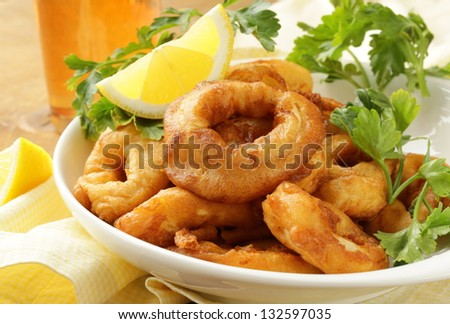 fried squid rings dipped in batter with lemon - stock photo