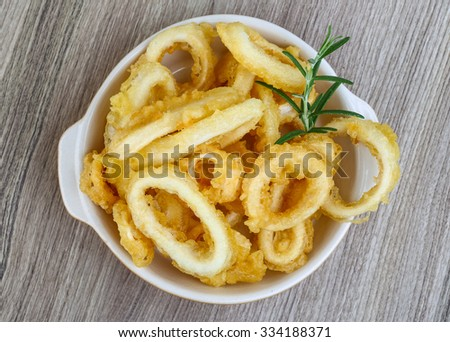 Fried squid rings with lemon, herbs and spices - stock photo