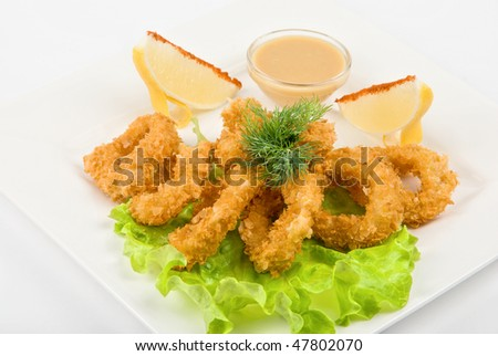 fried squid with salad leaves, sauce, green and lemon on a white background - stock photo