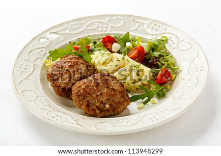 Fried steaks with mashed potatoes and vegetable salad - stock photo