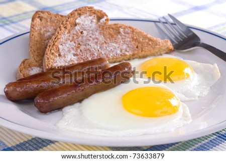 Fried sunny side up eggs with sausage links and buttered wheat toast.