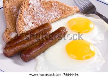 Fried sunny side up eggs with sausage links and buttered wheat toast. - stock photo