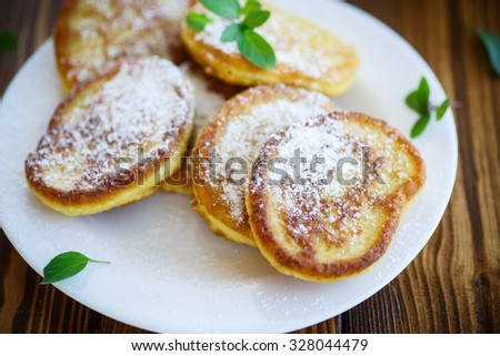 fried sweet pumpkin pancakes on a wooden table - stock photo