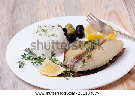 fried tilapia served with rice, olives, lemon and herbs on white plate. - stock photo
