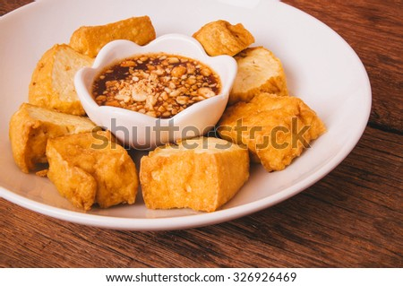 Fried Tofu, Crispy outside and Soft inside. Dip with Sweet Sour Tamarind Sugar Chilli Sauce, Top with Peanut Crusted. Wood Background, Rustic Still Life Style, Fresh Homemade Healthy Cooking Idea. - stock photo