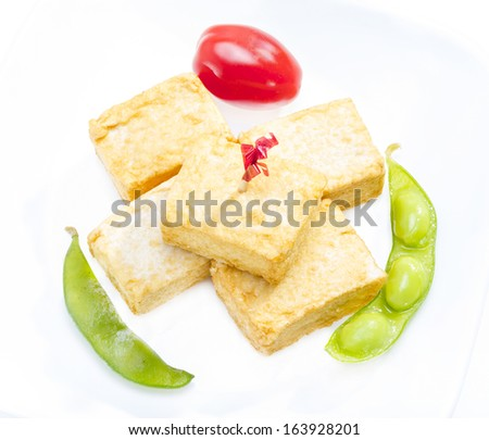 Fried tofu served with soy bean and tomato. - stock photo