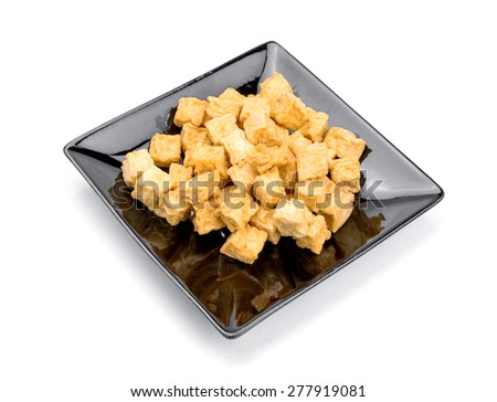 fried tofu, soy products on black plate bowl on white background