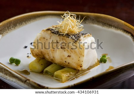 Fried toothfish with onion on dish - stock photo