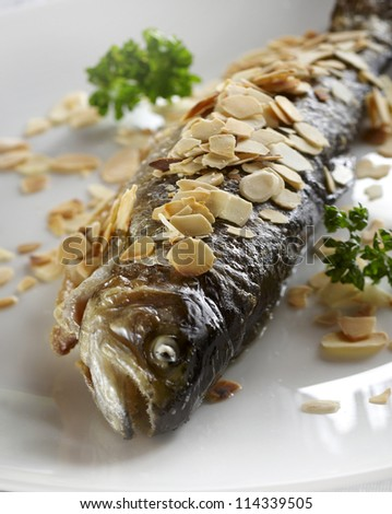 Fried trout with roasted almonds - stock photo