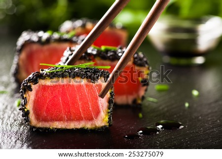 Fried tuna steak in black sesame with chopsticks - stock photo